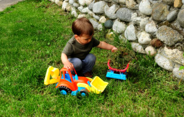 Young boy playing with toy truck in the grass.