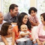 Hispanic family sitting on a couch, includes grandfather, grandmother, father, mother, boy,girl and baby