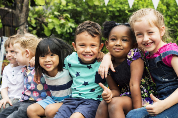 Six diverse children with arms around each other smiling