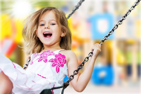 A young girl on a swing looks at the camera, smiling and laughing. Featured on Maryland Family Engagement Toolkit