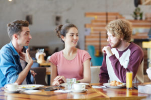 Three young adults sit at a cafe table with mugs in front of them, engaged in conversation