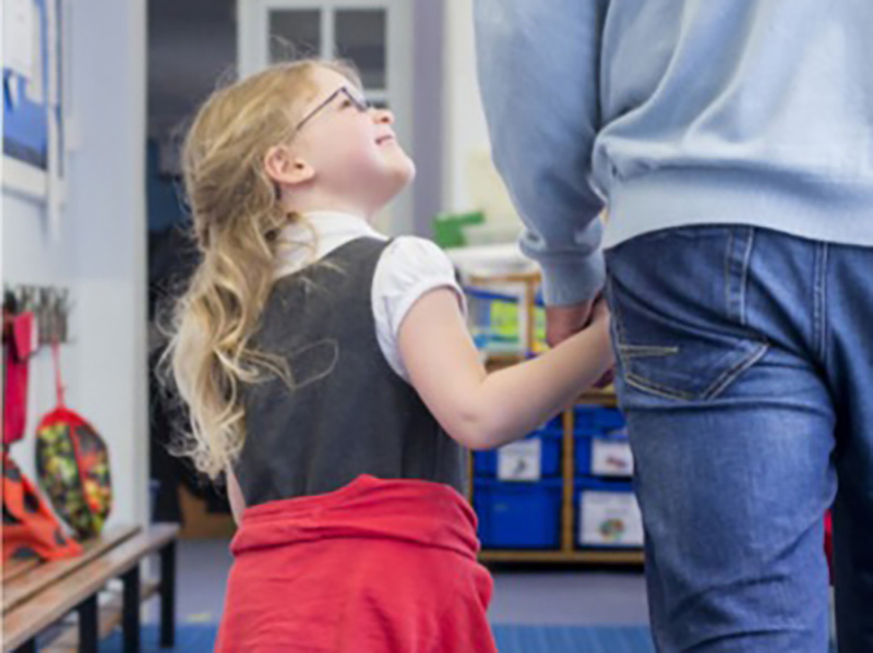 Gentle Transition Tips for parents of young children - ayoung girl holds her parent's hand and looks up to them as they walk into a classroom
