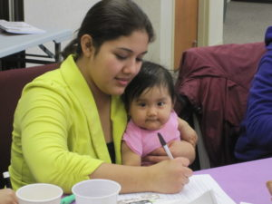 A Hispanic mother fills out paperwork with her infant girl in her lap.