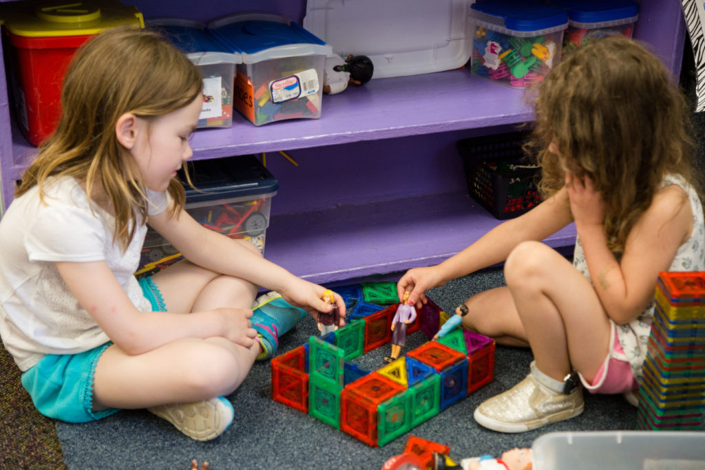 Two girls play together with magnetic tiles to make blocks.