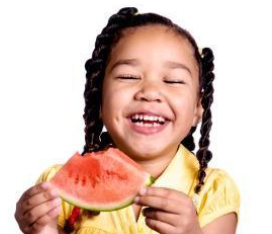 young girl eating watermelon while smiling