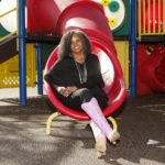 Educational expert and leader Dr. Rosemarie Allen sits at the bottom of a slide on a playground.