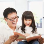 A father happily reads a book to his young daughter