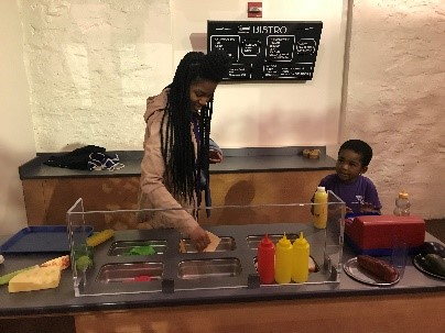 A young boy and a teacher make a sandwich at an exhibit at a children's museum