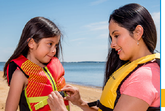 Mother helps girl with her life jacket
