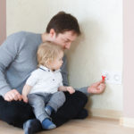 father sits on the floor with a toddler on his lap while putting in safety caps on the electrical socket