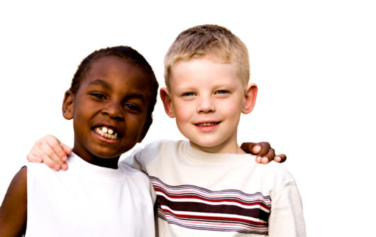 An african american boy and white boy stand arm in arm smiling