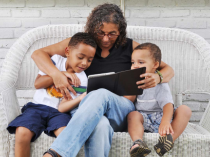 Woman sits on a couch with two young boys on both sides of her looking at a tablet