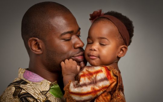 Man wearing african print shirt holds and kisses toddler with their eyes closed
