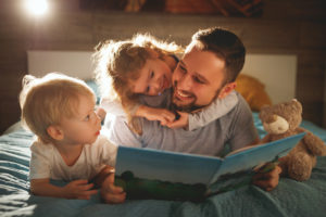 father, daughter and son lie on the bed reading a book together