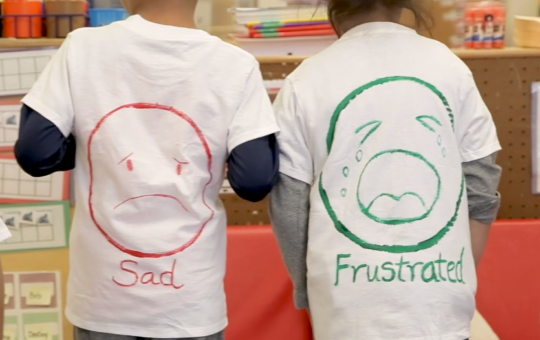 two children wearing shirts with painted sad and frustrated faces on them