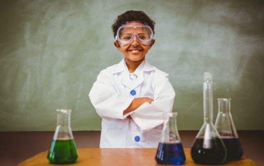 Boy wearing lab coat stands with arms crossed in front of a table with beakers filled with colored liquid