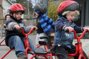 three preschool boys are riding tricycles in a playground