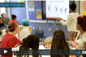 video screenshot showing a facilitator in front of a room full of parents and families