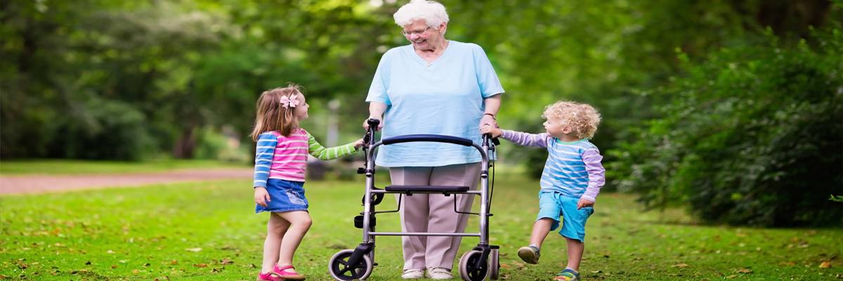 senior lady with a walker holding hands of little boy and girl