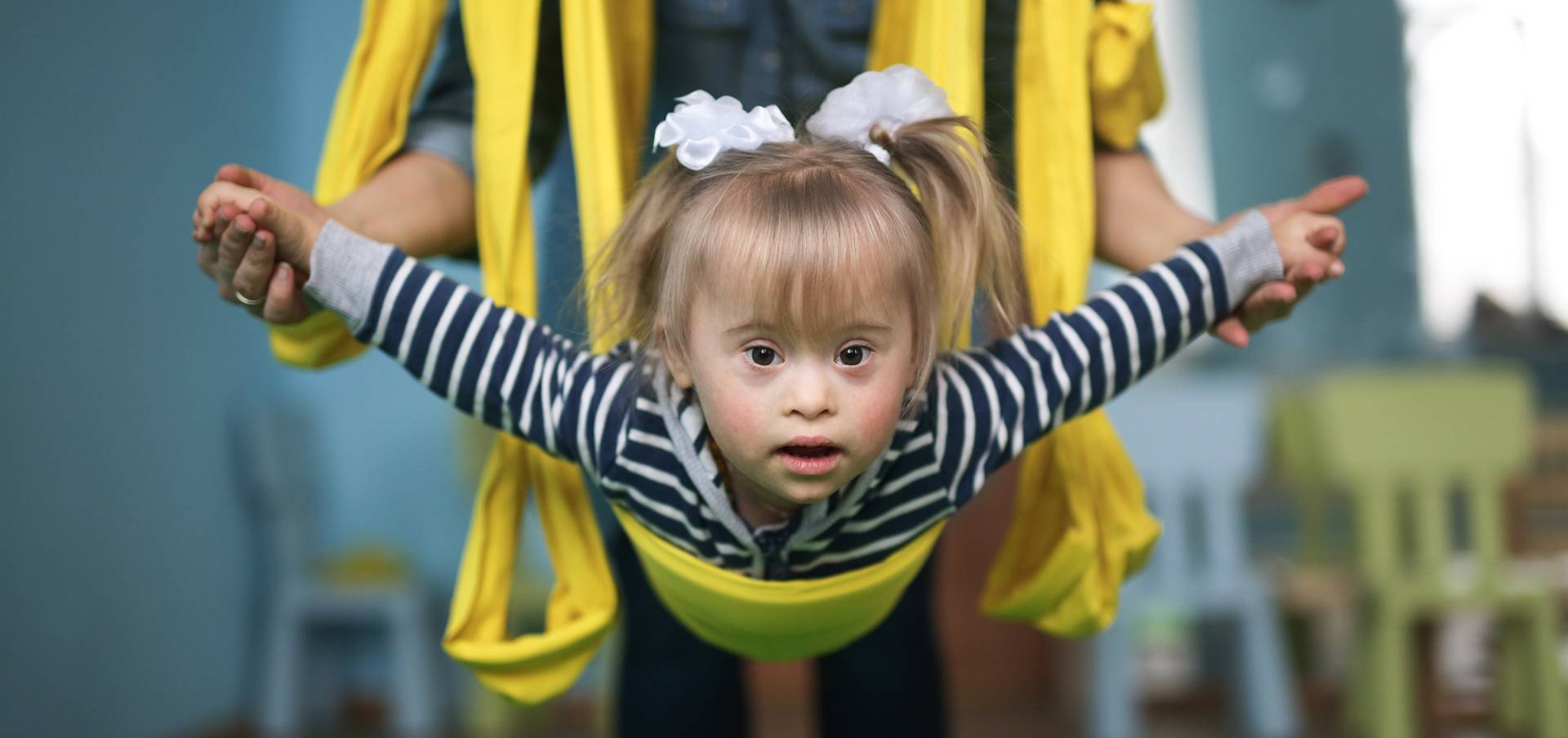 woman with child engaged in air yoga, yellow hammock,